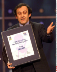 Former French player Michel Platini presents the FIFA trophy that shows the French soccer team on first position of the FIFA ranking during the awarding ceremony of the FIFA trophies 2001 in Zurich, Switzerland, on Monday, Dec. 17, 2001. (AP Photo/Key/SIP