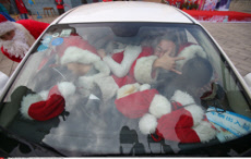 Changsha Participants dressed like Santa Claus are crammed into a car during a car loading game in the Colorful World Park of Changsha