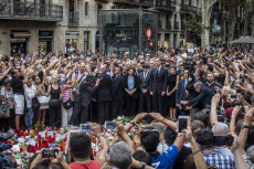 Spain's King Felipe and Queen Letizia wave to the crowd after paying respect at a memorial tribute of flowers, messages and candles to the van attack victims in Las Ramblas promenade