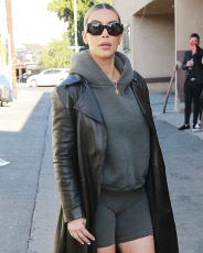 Kim Kardashian shows off her toned legs in biker shorts and leather trenchcoat as she stops by DASH store in Los Angeles