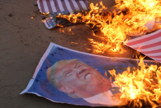 """Palestinian protesters burn portraits of US President Donald Trump during clashes in a tent city protest where Palestinians demand the right to return to their homeland, on the occasion of the 70th anniversary of the """"Nakba"""""""