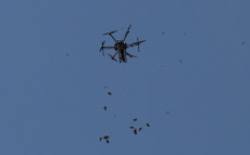 A picture taken on May 15, 2018 shows an Israeli quadcopter drone flying over Palestinian protesters and throw tear gas canisters during clashes in a tent city protest where Palestinians demand the right to return to their homeland