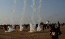 """Palestinian protesters run for cover from tear gas canisters fired by Israeli security forces during clashes in a tent city protest where Palestinians demand the right to return to their homeland, on the occasion of the 70th anniversary of the """"Nakba"""""""