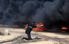 """Palestinian protesters gather during clashes with Israeli security froces in a tent city protest where Palestinians demand the right to return to their homeland, on the occasion of the 70th anniversary of the """"Nakba"""""""