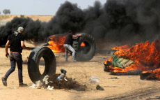 """Palestinians collect tires to be burnt during clashes in a tent city protest where Palestinians demand the right to return to their homeland, on the occasion of the 70th anniversary of the """"Nakba"""""""