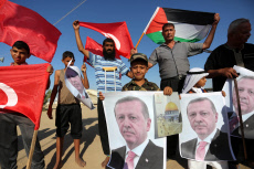 Palestinians hold portraits of Turkish President Recep Tayyip Erdogan during a rally to support with Turkey's presidential and parliamentary elections in Al-Bureij in the center of Gaza Strip