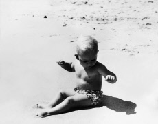 Prince Andrew as a baby on a sandy beach