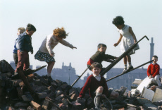 Children playing amid the piles of brick and wood