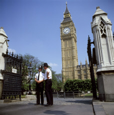 Policemen guarding Palace of Westminster with Big Ben