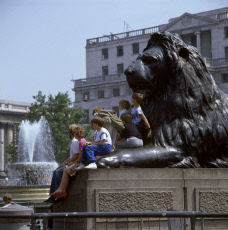 Children and adults sit on a Landseer Lion, Trafalgar Square