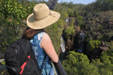 Woman tourist looking at lorence Falls in Litchfield National Park Northern Territory Australia