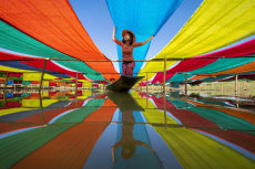 Huge strips of fabric create a rainbow of colour as they are laid out to dry.