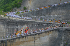 Hundreds of people dressed in white walk together on a winding road
