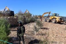 An Israeli bulldozer demolishes a Palestinian building which does not have the Israeli needed permits at al-Aroub camp