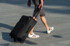 Young man with rolling suitcase