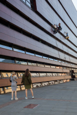 Two young women photograph climber at the National Forum for Music in Wroclaw